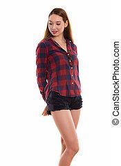 Studio shot of young beautiful Asian woman standing while lookin