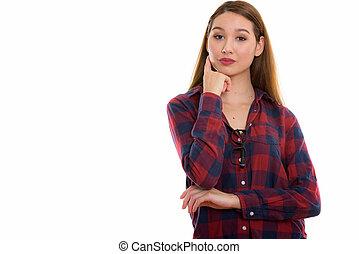 Studio shot of young beautiful Asian woman thinking
