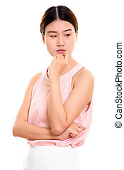 Studio shot of young beautiful Asian woman thinking while lookin