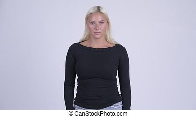 Studio shot of young beautiful blonde woman against white...