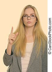Studio shot of young beautiful businesswoman pointing finger up