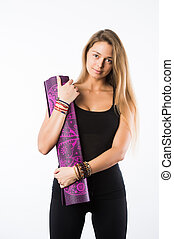 Studio shot of young beautiful teenage girl holding yoga mat and posing ready for gym