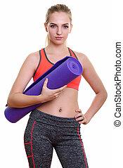 Studio shot of young beautiful teenage girl holding yoga mat and