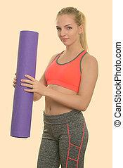 Studio shot of young beautiful teenage girl holding yoga mat ready for gym