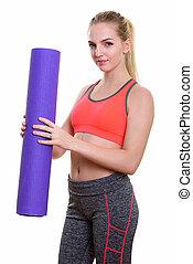 Studio shot of young beautiful teenage girl holding yoga mat rea