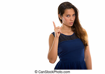 Studio shot of young beautiful woman pointing finger up