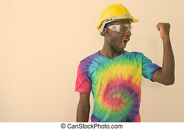 Studio shot of young black African man construction worker wearing hard hat and safety glasses while flexing his bicep against white background