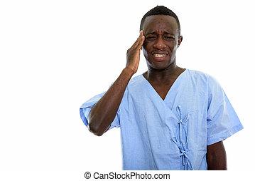 Studio shot of young black African man patient having headache