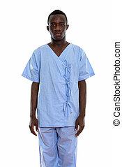 Studio shot of young black African man patient standing