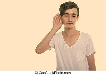 Studio shot of young handsome Persian teenage boy listening
