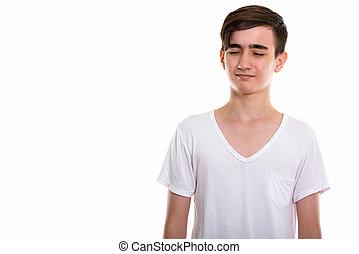 Studio shot of young handsome Persian teenage boy looking disgus
