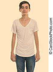 Studio shot of young handsome Persian teenage boy standing