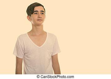 Studio shot of young handsome Persian teenage boy thinking