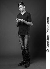 Studio shot of young handsome teenage boy