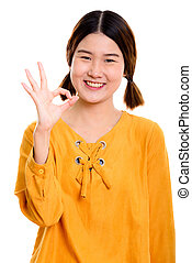 Studio shot of young happy Asian woman smiling while giving ok s