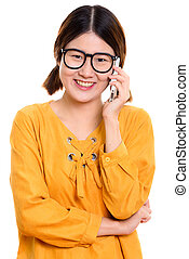 Studio shot of young happy Asian woman smiling while talking on