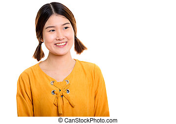 Studio shot of young happy Asian woman smiling while thinking