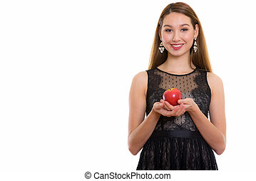 Studio shot of young happy beautiful Asian woman smiling while h