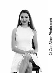 Studio shot of young happy beautiful Asian woman smiling while sitting on the chair