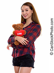 Studio shot of young happy beautiful Asian woman smiling while s