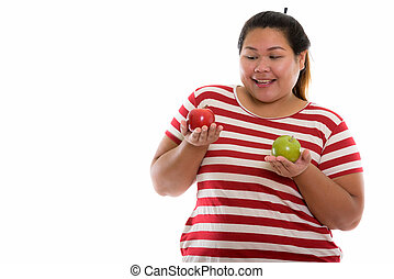 Studio shot of young happy fat Asian woman smiling while looking