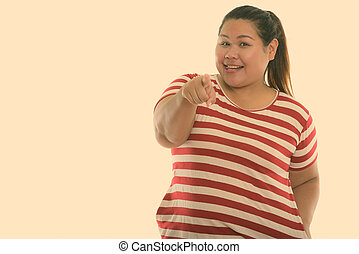 Studio shot of young happy fat Asian woman smiling while pointing at camera and sticking tongue out