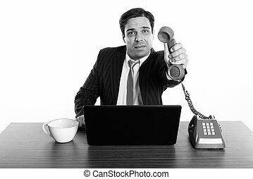 Studio shot of young Persian businessman giving old telephone with laptop and coffee cup on wooden table