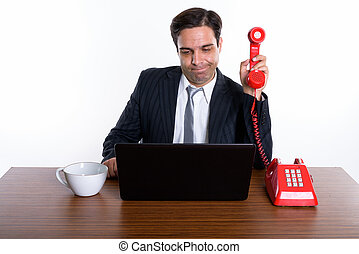 Studio shot of young Persian businessman holding old telephone a