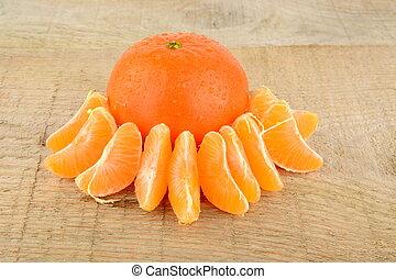 Studio shot pieces dewy mandarines on wooden table