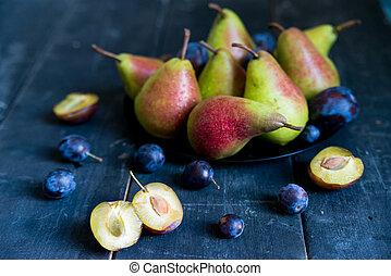 Studio shot plums and pears on plate heathy diet