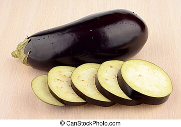 Studio shot single wet aubergine eggplant on wooden table