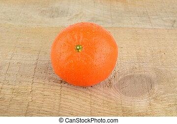 Studio shot wet tangerine isolated on wooden table