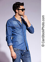 studio side view of a handsome young male model wearing jeans shirt and sunglasses