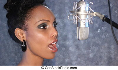 Attractive young woman sings into a professional, condenser microphone.