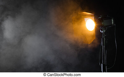 Studio spot light with smoke effect on black background