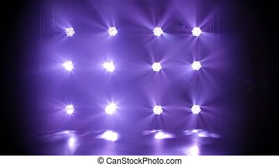 Studio spotlight or projector motion template. Dynamic purple light beams move to the right and left. Dark background. Lighting equipment. Shot for advertising, holiday or show