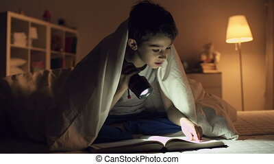 Studious Pupil - Static shot of boy sitting under blanket...