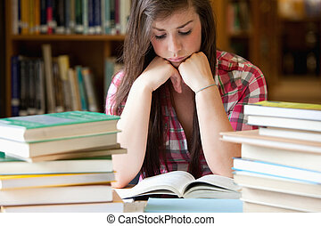 Studious woman surrounded by books