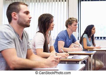 Studious young adults listening a lecturer in a classroom
