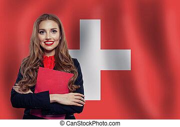 Study, internship and work in Switzerland concept. Beautiful smart woman on swiss flag background