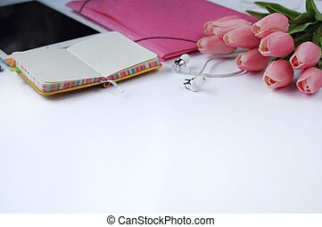 Study stuff. Education background. Stationery. Aspects of education. Tablet, folder, headphones, flowers and notebook on the table.