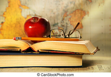 Old books with red apple and glasses on study desk