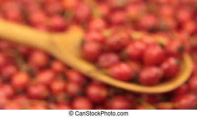 Study with a magnifying glass, rosehips in a wooden spoon,...