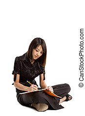 An isolated shot of a beautiful student studying and writing on a notebook