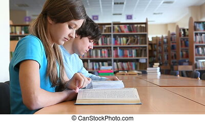 Studying at library - Two teens studying at library