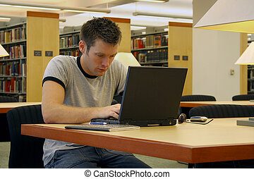 Studying - College student studying with laptop in the...