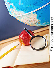 Studying geography composition of the red apple, old books, globe and magnifying glass against the blackboard background