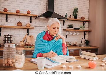 Grey-haired beautiful elderly lady in blue shawl looking concentrated