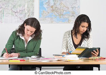 Studying hard - Two girls at school bend over their books