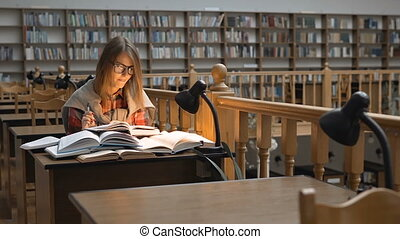 Studying in the Library - Pretty successful student girl...